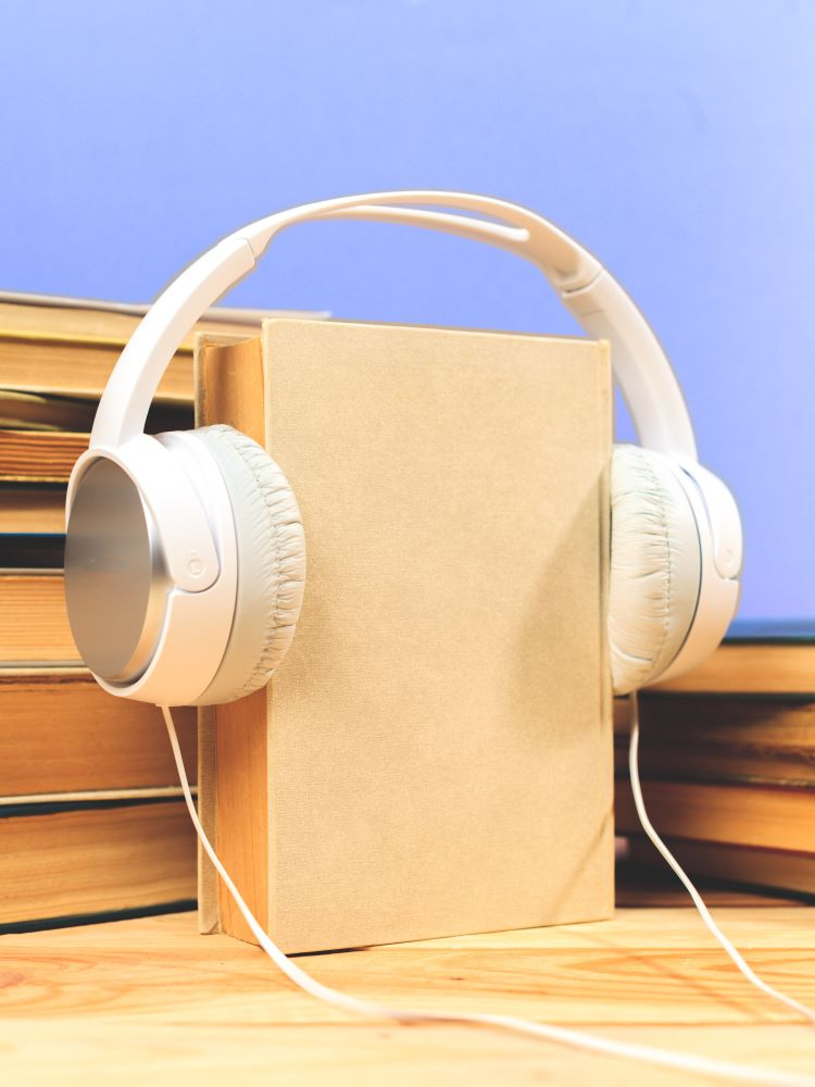 Audiobooks: image of two piles of books and one book with headphones on